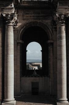 Pionowe ujęcie wnętrza świątyni z łukowym oknem i pięknym pejzażem w tle