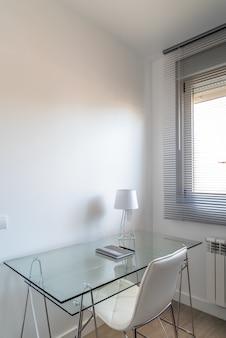 Pionowe ujęcie z dużym kątem, przedstawiające minimalistyczny biały pokój ze szklanym biurkiem w pobliżu okna