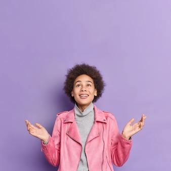 Pionowe ujęcie zadowolonej, dobrze wyglądającej, kręconej, afroamerykańskiej nastolatki z afroamerykanów rozkłada dłonie i patrzy powyżej