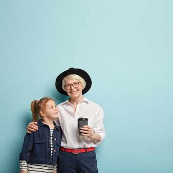 Pionowe ujęcie zadowolonej starszej kobiety obejmuje swoją małą wnuczkę, udziela rad, noś modne ubrania