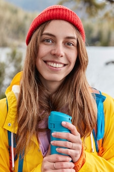 Pionowe ujęcie zadowolonej, uśmiechniętej kobiety, która nosi czerwone nakrycie głowy, żółty płaszcz przeciwdeszczowy, ogrzewa się gorącym napojem z termosu