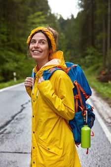 Pionowe ujęcie zadowolonej, uśmiechniętej młodej europejki nosi żółtą opaskę, płaszcz przeciwdeszczowy i nosi plecak