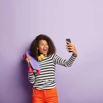 Pionowe ujęcie zadowolony african american millennial girl bierze selfie