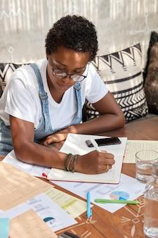 Pionowe ujęcie zajętego dyrektora finansowego analizuje informacje w gazetach, zapisuje je w notatniku