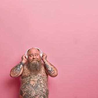 Pionowe ujęcie zamyślonego brodatego mężczyzny wygląda na zadowolonego powyżej, trzyma ręce na słuchawkach, myśli o czymś przyjemnym słuchając muzyki, ma problem z otyłością, wytatuowane nagie ciało, tęgi brzuch