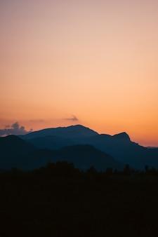Pionowe ujęcie zapierającego dech w piersiach zachodu słońca nad lasem otoczonym górami