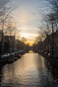 Pionowe ujęcie zapierającego dech w piersiach zachodu słońca nad rzeką w południowo-wschodnim amsterdamie