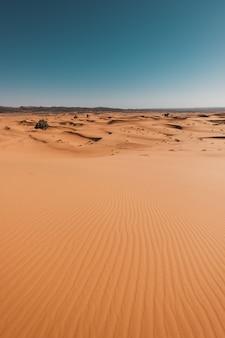 Pionowe ujęcie zapierającej dech w piersiach pustyni pod błękitne niebo uchwycone w maroku