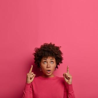 Pionowe ujęcie zawstydzonej zszokowanej kobiety afroamerykanki wskazuje palce wskazujące w górę, pod wrażeniem czegoś oszałamiającego, pokazuje puste miejsce na różowej ścianie, stoi bez słowa w pomieszczeniu