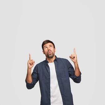 Pionowe ujęcie zdziwionego, nieogolonego faceta wskazuje palcami wskazującymi w górę