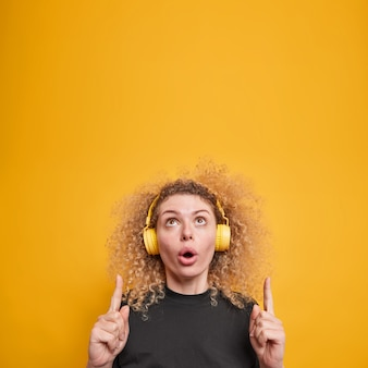 Pionowe ujęcie zdziwionej, zdziwionej młodej kobiety z kręconymi włosami powyżej pokazuje niesamowitą reklamę słuchającą muzyki przez słuchawki, ubraną w swobodną żółtą koszulkę na białym tle nad żółtą ścianą