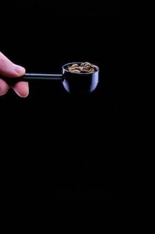 Pionowe ujęcie ziaren kawy w czerpaku kawy samodzielnie na czarnym tle