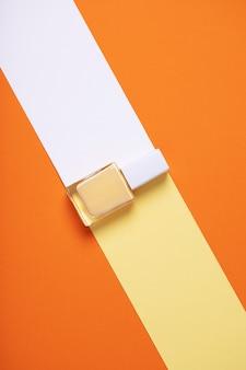 Pionowe ujęcie żółtej butelki lakieru do paznokci na geometrycznym kolorowym tle
