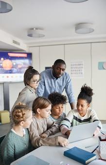 Pionowe ujęcie zróżnicowanej grupy dzieci korzystających razem z laptopa przy stole w nowoczesnej szkole