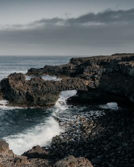 Pionowe wysoki kąt strzału skalistego brzegu morza w ponury dzień