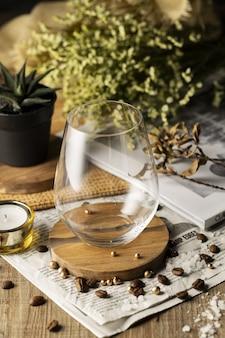 Pionowe, wysokie ujęcie pustej szklanki na pięknie zdobionym drewnianym stole