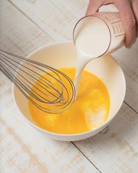 Pionowe zbliżenie dłoni nalewającej mleko na miskę jajka, trzymając trzepaczkę do jajek