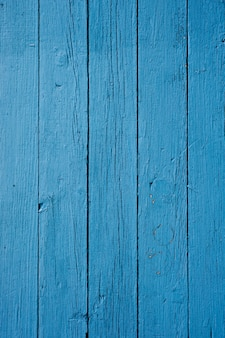 Pionowe zbliżenie drewnianej ściany pomalowanej na niebiesko pod światłami