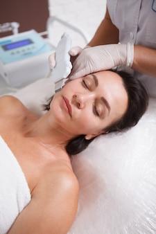Pionowe zbliżenie kobiety wykonującej peeling ultradźwiękowy przez kosmetyczkę