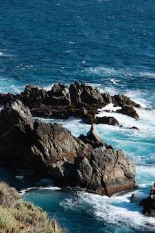 Pionowe zbliżenie malowniczego widoku fal zderzających się z gigantycznymi skałami w oceanie