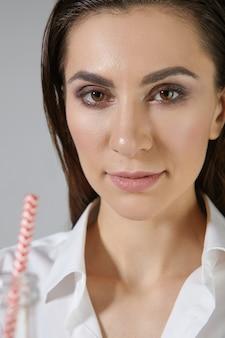 Pionowe zbliżenie obrazu pięknej ciemnowłosej młodej kobiety makijaż na sobie białą koszulę, patrząc i uśmiechając się, trzymając szklaną butelkę ze słomką, odświeżając się, pijąc lemoniadę