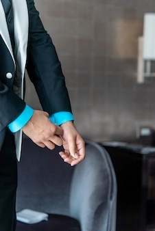 Pionowe zbliżenie strzał mężczyzny ustalającego niebieski rękaw kostiumu