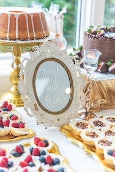 """Pionowe zbliżenie strzał stołu deserowego z napisem """"sweets and treats"""" na ramce"""