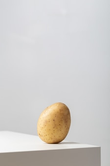 Pionowe zbliżenie surowego ziemniaka na stole pod światłami na białym tle