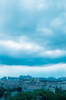 Pionowe zdjęcia lotnicze wysokich budynków miejskich pod zachmurzonym niebem