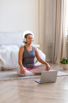 Pionowe zdjęcie afroamerykanki medytującej w domu przed monitorem laptopa i słuchając muzyki przez słuchawki.