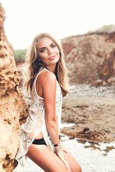 Pionowe zdjęcie atrakcyjnej blondynki z długimi włosami, pozowanie do kamery na tle skał. ona się uśmiecha.