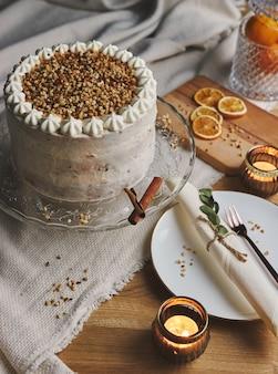 Pionowe zdjęcie białego pysznego tortu bożonarodzeniowego z orzechami i mandarynką