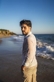 Pionowe zdjęcie brunetki mężczyzny na falującym oceanie