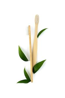 Pionowe zdjęcie dwie szczoteczki do zębów wykonane z ekologicznego materiału z zielonymi liśćmi na białym tle