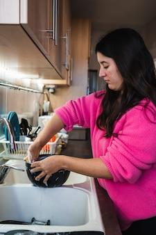 Pionowe zdjęcie dziewczyny z długimi włosami i różowym swetrem myjącym miskę w kuchni