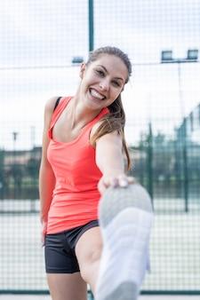 Pionowe zdjęcie kobiety w odzieży sportowej, rozciąga nogę na tenisie odkrytym