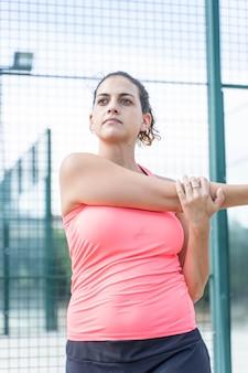 Pionowe zdjęcie kobiety w odzieży sportowej, rozciąga ręce na korcie tenisowym