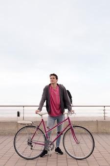 Pionowe zdjęcie młodego mężczyzny trzymającego rower retro