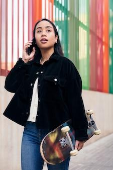 Pionowe zdjęcie młodej azjatyckiej dziewczyny rozmawiającej przez telefon podczas spaceru ulicą z deskorolką w dłoni