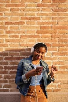 Pionowe zdjęcie młodej kobiety african american ze słuchawkami, słuchanie muzyki, śpiew i taniec