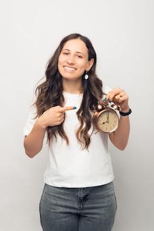 Pionowe zdjęcie młodej kobiety, wskazując na budzik.