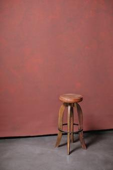 Pionowe zdjęcie okrągłego rocznika stołka ze skórzanym siedzeniem na czerwonym tle z copyspace. stare drewniane krzesło w studio fotograficznym