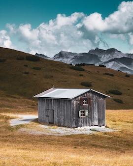 Pionowe zdjęcie opuszczonego drewnianego domu w szczerym polu