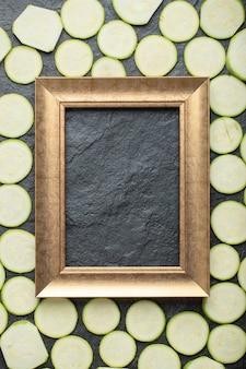 Pionowe zdjęcie pf pokrojone w plasterki cukinii wokół ramki.