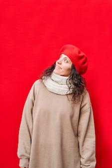 Pionowe zdjęcie pięknej eleganckiej wesołej kobiety, uśmiechającej się i patrząc w górę z odizolowaną czerwoną ścianą