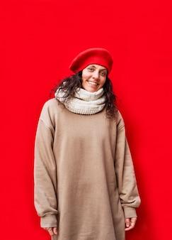 Pionowe zdjęcie pięknej i eleganckiej szczęśliwej i świątecznej kobiety z odizolowaną czerwoną ścianą