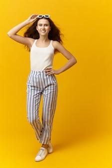 Pionowe zdjęcie pięknej, radosnej młodej kobiety w modnych, modnych ubraniach i akcesoriach
