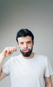 Pionowe zdjęcie poważnego zabawnego spokojnego faceta bawiącego się szczoteczką do zębów. trzymaj go między ustami a nosem. koncepcja opieki zdrowotnej
