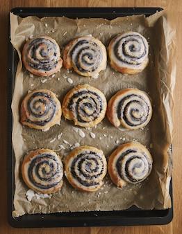 Pionowe zdjęcie pysznych ciastek makowych ślimaka z polewą cukrową na tacy na drewnianym stole