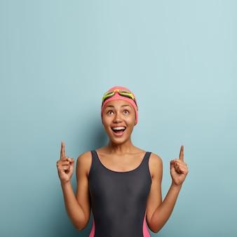 Pionowe zdjęcie radosnej ciemnoskórej kobiety, która lubi ulubione hobby i letni aktywny wypoczynek, ubrana w strój kąpielowy